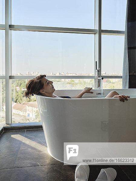Entspannte ältere Frau im Ruhestand  die ein Bad in einer Badewanne vor dem Fenster eines Luxushotels nimmt Entspannte ältere Frau im Ruhestand, die ein Bad in einer Badewanne vor dem Fenster eines Luxushotels nimmt