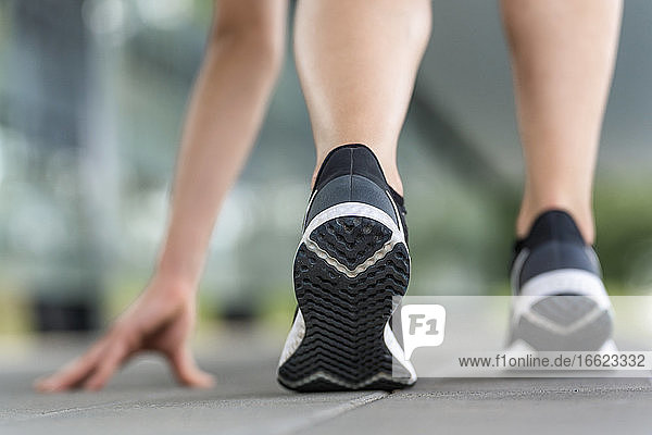 Legs of young woman exercising on footpath