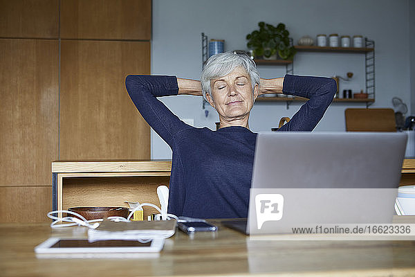 Senior woman with hands behind head relaxing while sitting at home