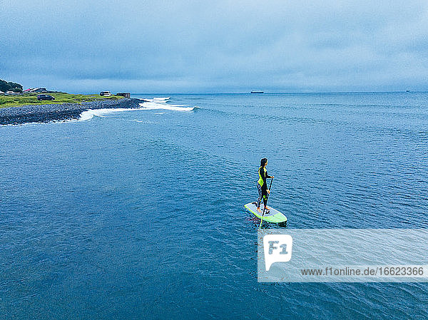 Aerial view of young woman paddleboarding near coast in Sea of Japan