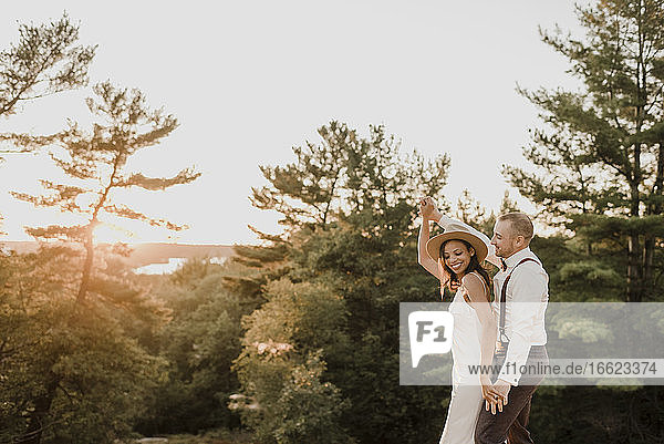 Bride and bridegroom dancing in forest during sunset