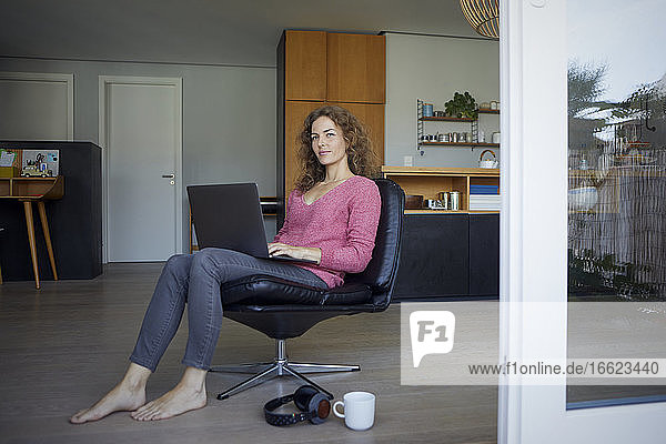 Mid adult woman working on laptop while sitting on chair at home