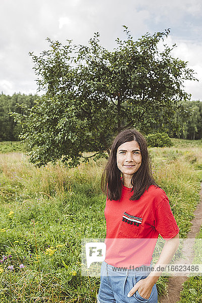 Smiling mid adult woman standing on grassy landscape