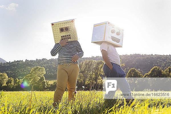 Junge spielt  während er sein Gesicht mit einem Roboterkarton bedeckt Junge spielt, während er sein Gesicht mit einem Roboterkarton bedeckt