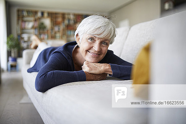 Smiling senior woman with hand on chin lying on sofa at home