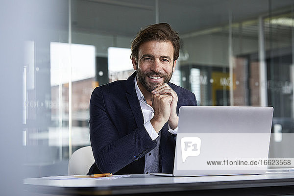 Smiling businessman using laptop while sitting on chair in office