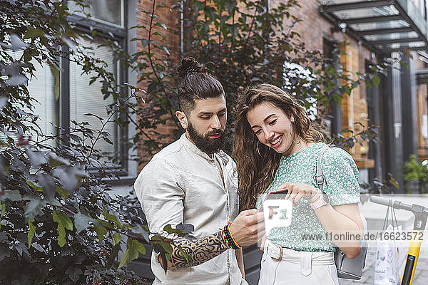 Couple looking at smart phone while standing footpath in city