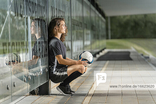 Thoughtful female soccer player holding ball while crouching by glass wall on footpath