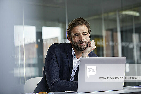 Businessman with head in hands leaning on desk while sitting in office