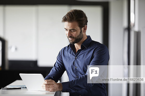 Businessman using digital tablet while standing at desk in office