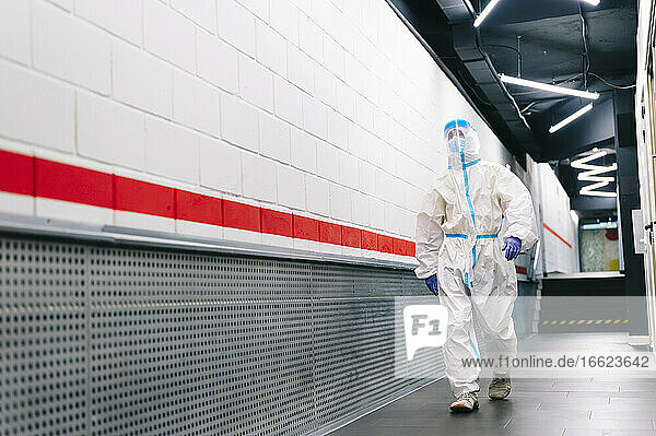 Man walking with face shield in corridor at hospital