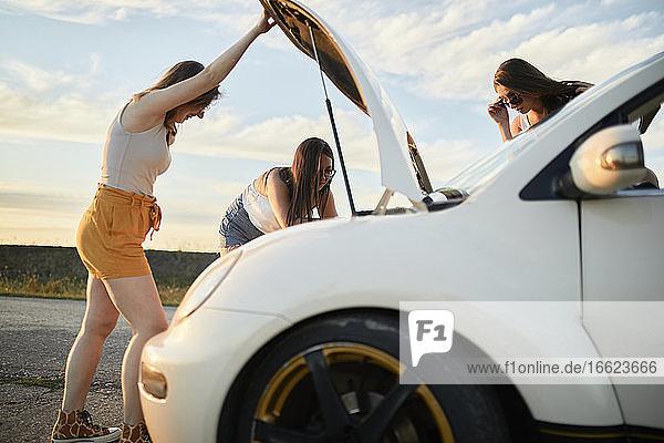Junge Freunde reparieren ihr Auto  während sie einen Roadtrip machen Junge Freunde reparieren ihr Auto, während sie einen Roadtrip machen