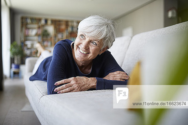 Smiling senior woman looking away with arms crossed while lying on sofa at home