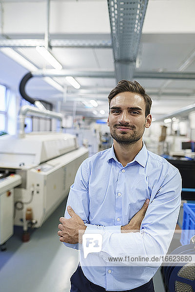 Young businessman standing with arms crossed at illuminated factory