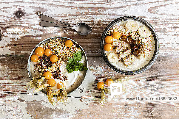 Two bowls of porridge with oats  flax seed  winter cherries and bananas