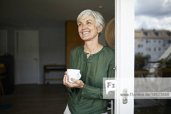Senior woman looking away standing with coffee cup by window at home