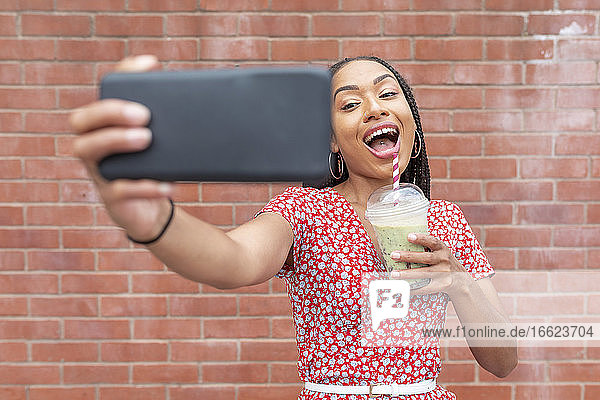 Young woman taking selfie while drinking smoothie against brick wall