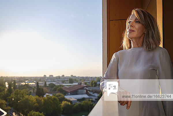 Senior woman looking away while standing in balcony