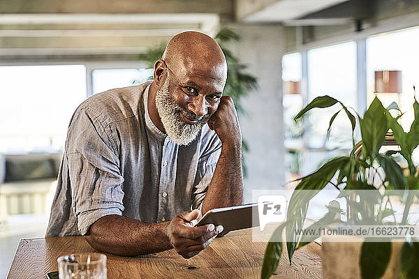 Smiling mature man holding digital tablet while leaning on table at building terrace