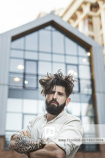 Hipster man standing with arms crossed against building in city