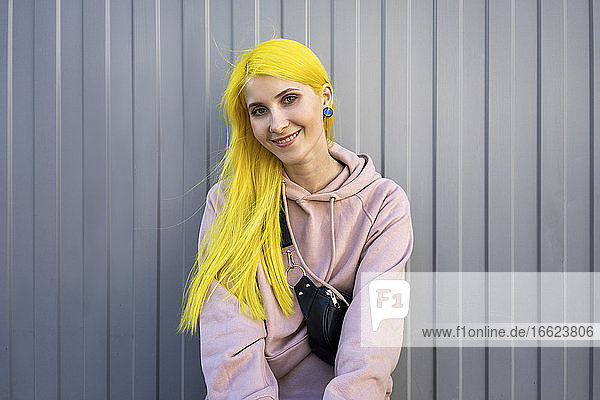 Smiling young woman standing against metal wall on sunny day
