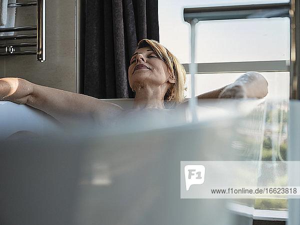Entspannte blonde ältere Frau  die ein Bad in der Badewanne vor dem Fenster eines Luxushotelzimmers nimmt Entspannte blonde ältere Frau, die ein Bad in der Badewanne vor dem Fenster eines Luxushotelzimmers nimmt