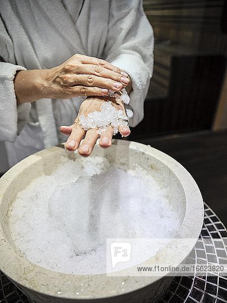 Mittelteil einer älteren Frau  die im Spa Eis auf die Hände reibt Mittelteil einer älteren Frau, die im Spa Eis auf die Hände reibt