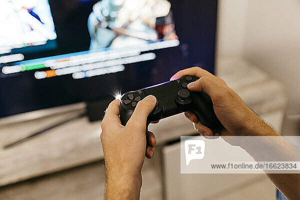 Hands of male gamer holding controller while playing at home