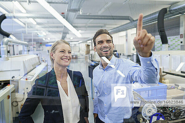 Happy young male technician pointing at graphical interface on glass in factory