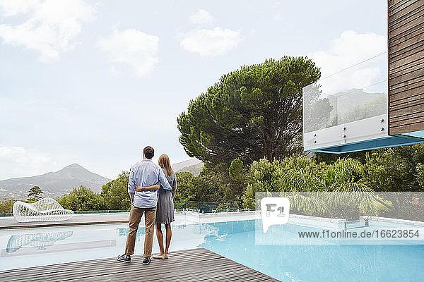 Heterosexuelles Paar  das in der Nähe des Schwimmbeckens steht und die Aussicht betrachtet Heterosexuelles Paar, das in der Nähe des Schwimmbeckens steht und die Aussicht betrachtet