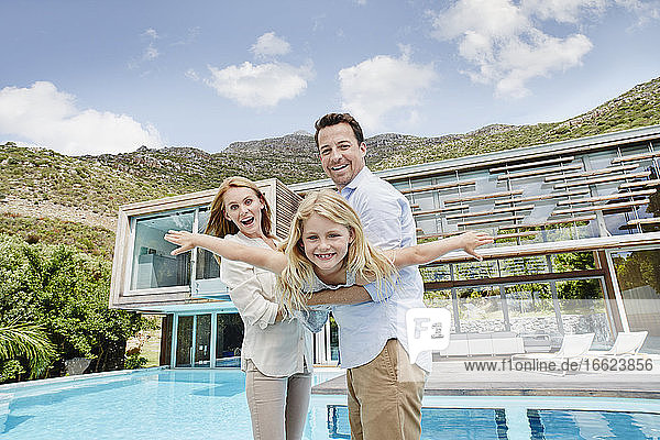 Mother and father enjoying with daughter while standing against modern house