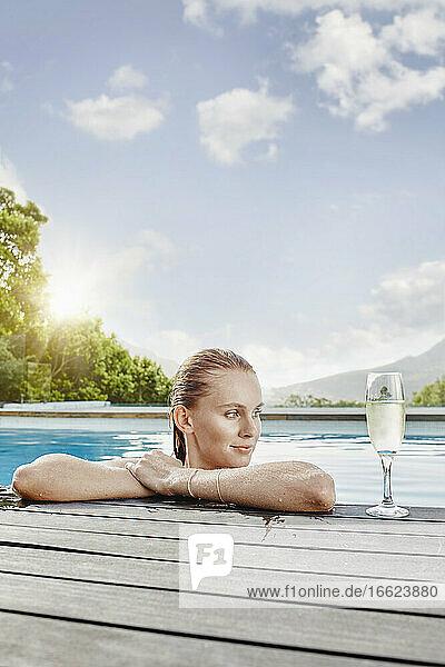 Junge Frau schaut weg  während sie im Pool liegt Junge Frau schaut weg, während sie im Pool liegt