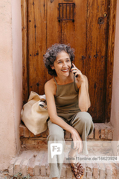 Mature woman talking on smart phone while sitting on doorway