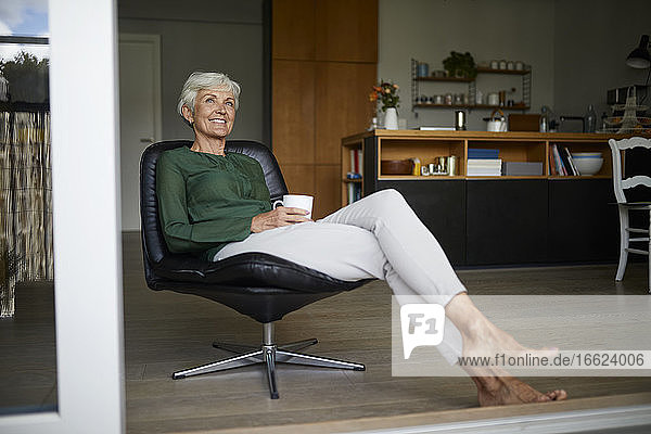 Senior woman looking away while holding coffee cup at home