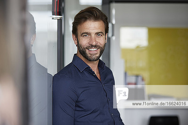 Man smiling while leaning on wall in office