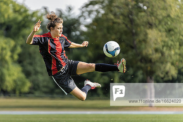 Young woman playing soccer in field