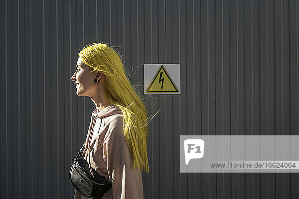 Young woman looking away while standing by metal wall on sunny day