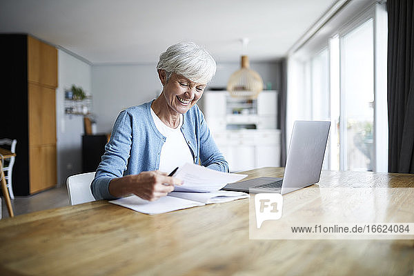 Smiling active senior woman doing paper work while sitting at home