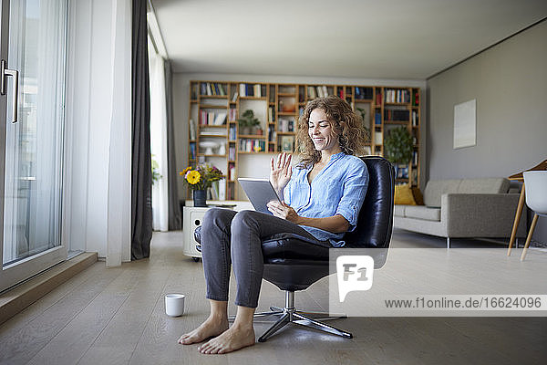 Smiling woman waving hand to video call on digital tablet while sitting on chair at home