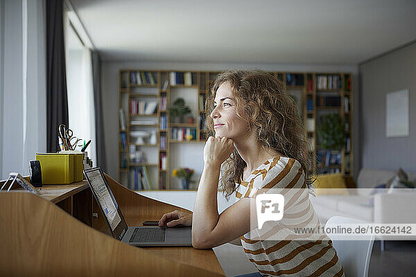 Smiling woman with head in hands sitting by desk at home