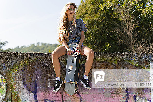 Thoughtful blond woman with skateboard sitting on surrounding wall at park
