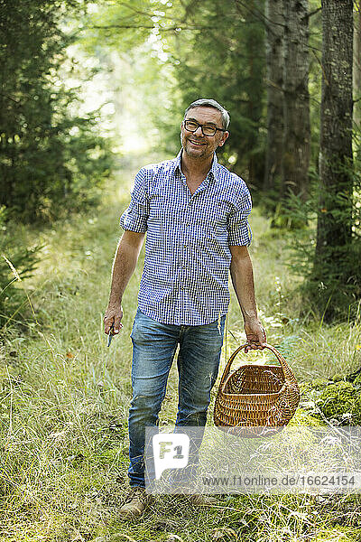 Smiling man holding basket while standing in forest