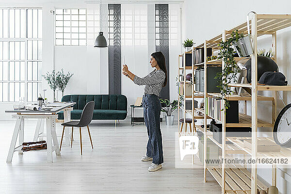 Female architect taking selfie from digital tablet while standing against rack at office