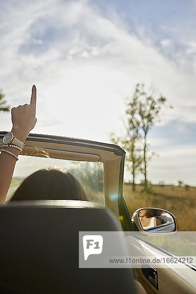 Young woman pointing up while sitting in convertible car