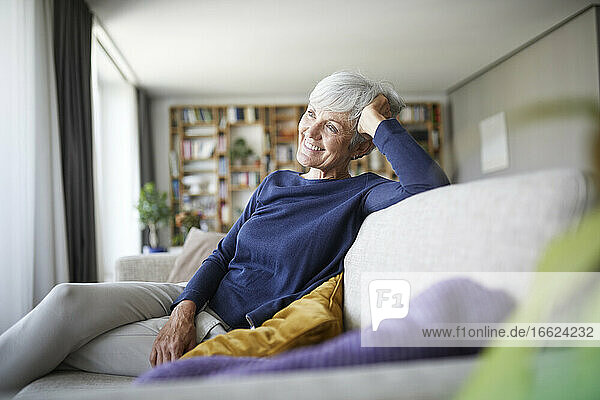 Smiling senior woman with head in hand sitting on sofa at home