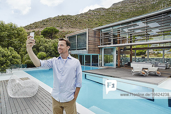 Älterer Mann  der ein Selfie mit seinem Smartphone macht  während er vor einem modernen Haus steht Älterer Mann, der ein Selfie mit seinem Smartphone macht, während er vor einem modernen Haus steht