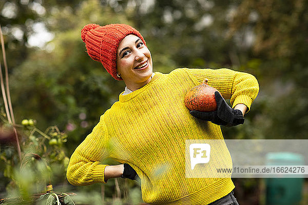 Smiling woman holding pumpkin while standing at urban garden
