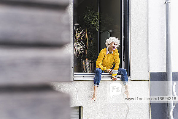 Mature woman holding coffee cup while sitting on window