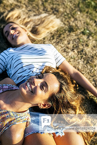 Cheerful young women relaxing on field during sunny day