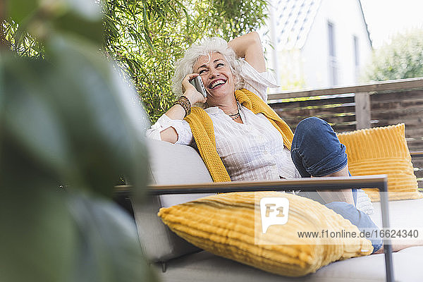 Mature woman talking on smart phone while sitting in balcony